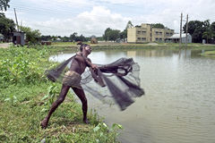 孟加拉国的渔夫投掷的捕鱼网在湖 免版税库存图片