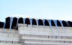 季节、住房和冬天概念-垂悬在门面r的冰柱 库存照片