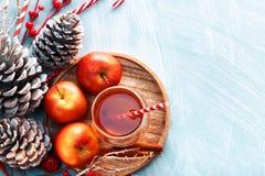 季节性和假日概念 在一块玻璃的冬天热的茶用苹果和香料在木背景 选择聚焦,顶视图 免版税库存图片