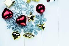季节性圣诞节装饰品和雪花在白色木背景 免版税库存图片