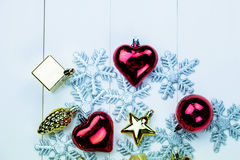 季节性圣诞节装饰品和雪花在白色木背景 免版税库存照片