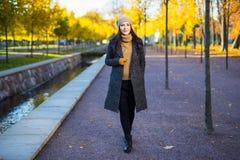 季节性概念-走在秋天公园的可爱的妇女 库存图片