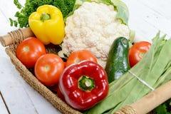 季节性菜篮子在白色木桌上的 图库摄影