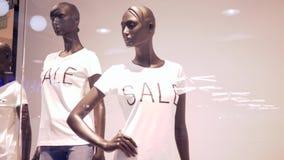 季节性销售,时装模特到有折扣题字通知的衣物里在陈列窗后的在商店 影视素材