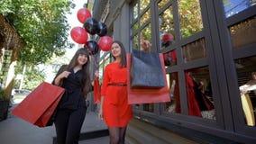 季节性销售,有袋子的愉快的时尚女孩沟通,当通过精品店窗口的购物和步行在黑色时 股票视频