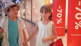 季节性销售,有购物包裹的快乐的儿童朋友去通过与时装模特的商店窗口在精品店 影视素材