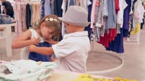 季节性销售,顾客在时尚商店哄骗措施新的衣物周末 影视素材