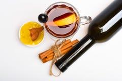 季节性饮料概念 玻璃用被仔细考虑的酒或热的饮料用葡萄、桂香和蜂蜜,白色背景,关闭 库存图片