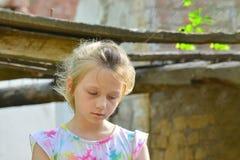孤儿女孩留给在大厦的废墟的附近无家可归和身分由于一次军事冲突、火和ea 免版税库存图片