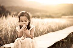 孤独和哀伤的小女孩坐竹走道 图库摄影