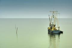 孤独小船的渔夫 免版税库存照片