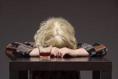 孤独的中年妇女喝一些白兰地酒酒精和头  库存图片