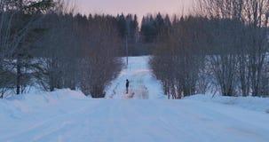 孤独的人在一条离开的冬天路站立在日落 影视素材