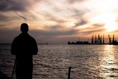 孤独的人在日落背景的船坞站立并且看海 免版税库存照片