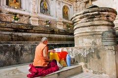孤独的人在老梵语语言读了佛教书 免版税库存图片
