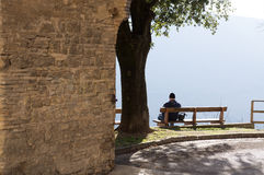 孤独的人坐长凳有山的美丽的景色 公园和森林 免版税库存照片