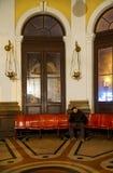 孤独的人睡着在驻地的候诊室 库存照片