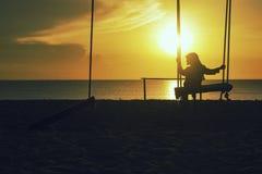 孤独的女孩剪影有hijab的在与不可思议的太阳的摇摆 免版税库存图片