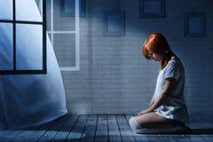 孤独的女孩在一个暗室 免版税库存照片