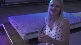 孤独的女孩在夜总会喝一个鸡尾酒坐夏天大阳台 年轻金发碧眼的女人享受俱乐部大气 股票视频