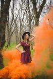 孤独的女孩在橙色烟的森林 库存图片
