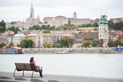 孤独的女孩坐长凳在布达佩斯的堤防 免版税库存照片