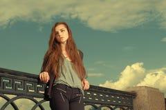 孤独的女孩等待某人谈话 穿浅灰色的毛线衣,染黑裤子, youg美国妇女支持的金属 免版税图库摄影