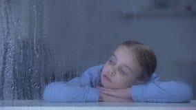 孤独的女孩说谎在窗口基石的在下雨天,作梦关于家的孤儿孩子 股票视频