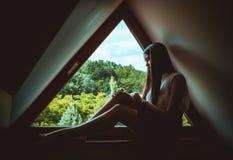 孤独的妇女坐窗口 库存图片