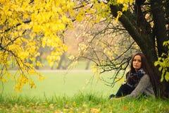 孤独的妇女有休息在树下在水附近在一有雾的秋天天 免版税库存照片
