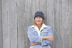 孤独的妇女温暖的夹克木材背景 免版税库存图片