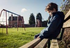 孤独的孩子坐戏剧公园操场长凳 免版税库存图片