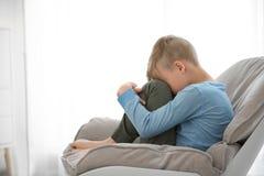 孤独的小男孩在家坐椅子 免版税库存照片