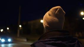 孤独的年轻人在夜城市附近走 股票录像