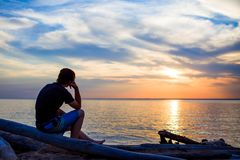 孤独的年轻人在海边 库存图片