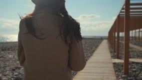孤独的年轻女人在海岸漫步自白天、边和后面看法 股票录像