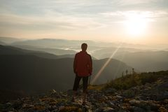 孤独的旅客站立在峭壁边缘 库存照片