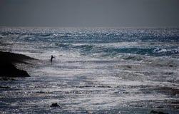 孤独的渔夫在奥阿胡岛中,夏威夷,淡光的波浪水域  免版税库存图片