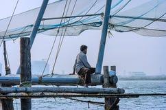 孤独的渔夫坐一个木渔平台 库存照片