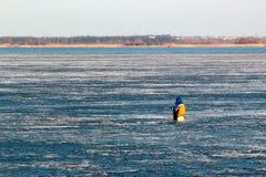 孤独的渔夫坐冻冰 免版税库存照片