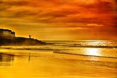 孤独的渔夫钓鱼在大西洋海岸的海滩 库存图片