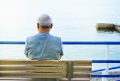 孤独的灰发的年长人由海坐长凳,从后面的一个自然的看法,沉思和一个松弛假日 库存图片