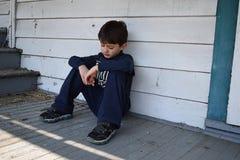孤独的男孩减少房子外 库存图片