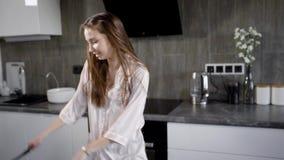 孤独的疯狂的主妇在拿着服务匙子和翻板的厨房跳舞在晚上,佩带在晨衣 股票视频