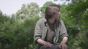孤独的紧张的年轻人坐长凳在等待他的朋友或女朋友的公园 人为做准备 股票录像
