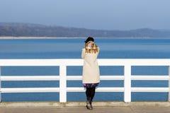 孤独的美丽的哀伤的女孩在码头站立在一个晴朗的温暖的秋天晚上在海 免版税库存图片
