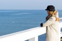 孤独的美丽的哀伤的女孩在码头站立在一个晴朗的温暖的秋天晚上在海 库存图片