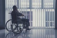 孤独的老人在家坐轮椅 免版税库存照片