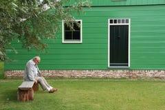 孤独的老人坐在绿色之外的长凳绘了房子 库存图片