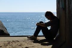 孤独青少年的在海滩的女孩和悲伤 库存照片